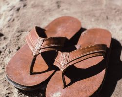 brown leather sandals on sand
