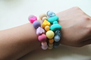 person wearing silver and pink beaded bracelet